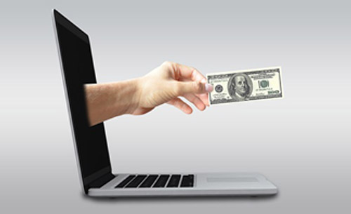 Hand with money emerges from laptop